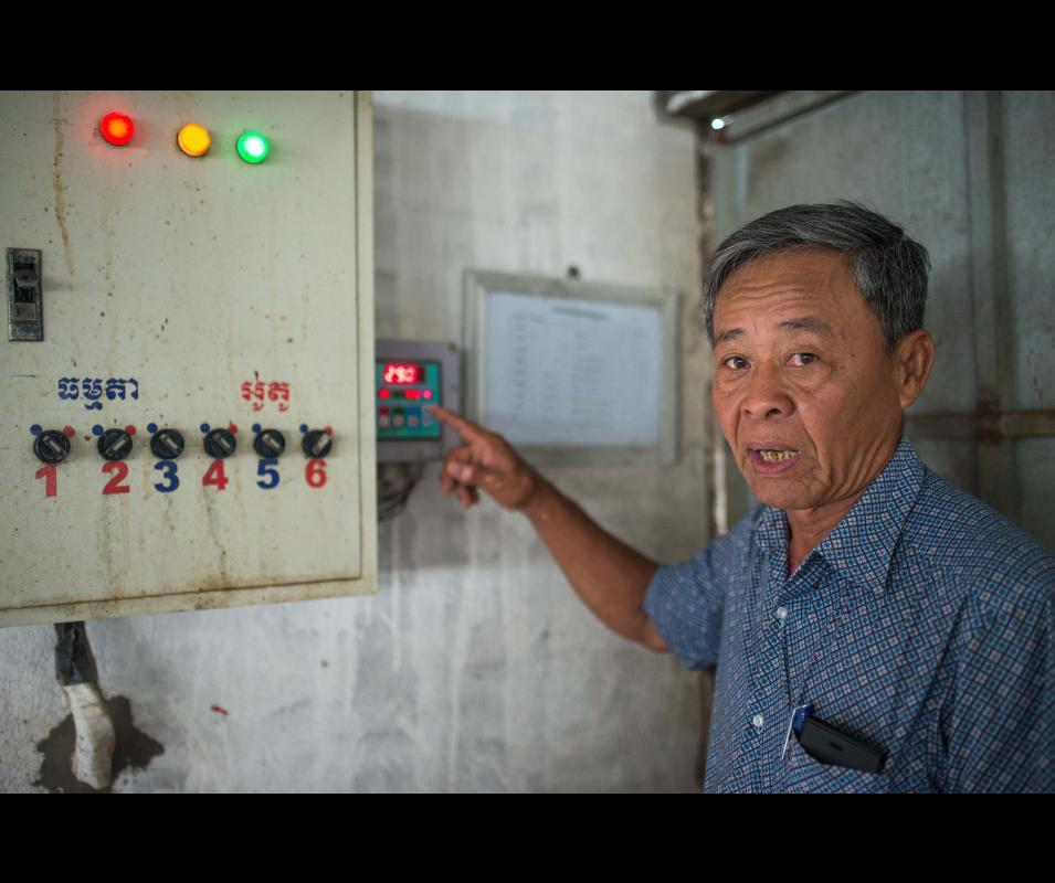Mr. Chhang Touch checking the temperature in pig's pen at his pig farm in Kompong Speu province, Cambodia. ©Kimlong Meng